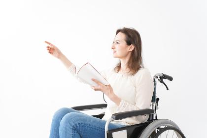 車椅子に乗り読書をする外国人の女性