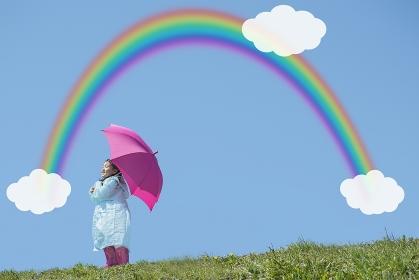 ピンクの傘をさす女の子と虹と雲