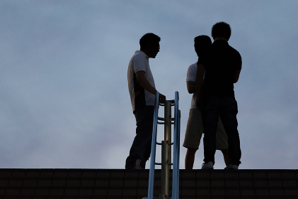 階段の上で話す3人の男性のシルエット