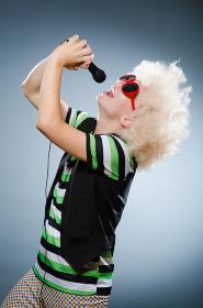 Man in afrowig singing with mic