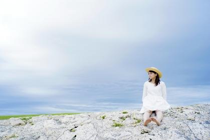 海辺の岩に座る日本人女性