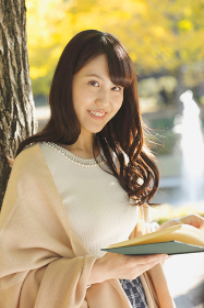 秋の公園で本を読む日本人女性