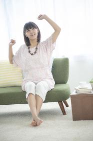 ソファーで伸びをする女性