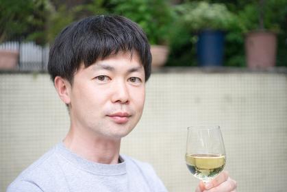 白ワインを飲む男性(笑顔・表情)