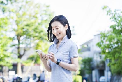 屋外でスマートフォンを操作する中年女性