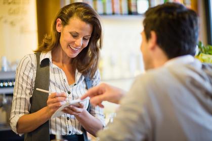 Woman taking orders in a café