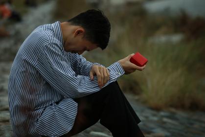 リングケースを手に持ち涙を流す男性