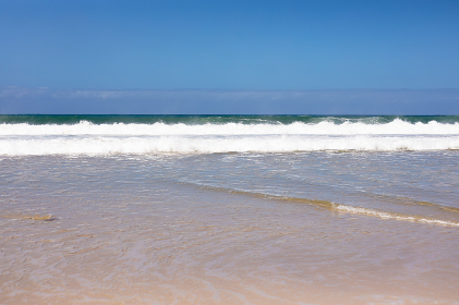 Beautiful beach by the sea and with big waves and golden sand on a sunny day. beautiful view of sunny coast