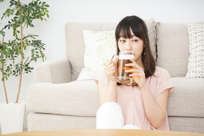 自宅でビールを飲む若い女性