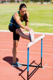 Female athlete warming up above hurdle