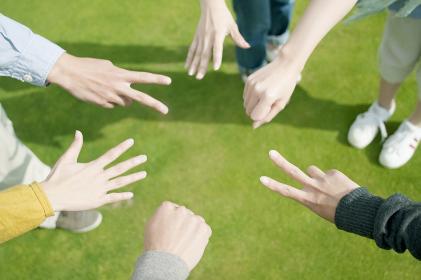 草原でジャンケンをする若者たちの手元