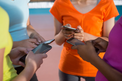 Female players using mobile phones in volleyball court