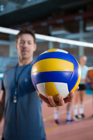 Coach holding volleyball in the court