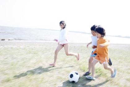 砂浜でサッカーをする子供たち