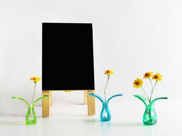 プラスチッククリップに挟んだ黄色い花と黒色の立て看板のコピースペース