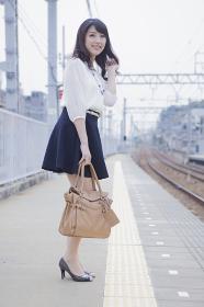 ホームで電車を待つ女性