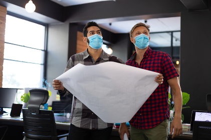 Diverse male colleagues wearing masks holding architectural plans in office. hygiene in workplace during coronavirus covid 19 pandemic.
