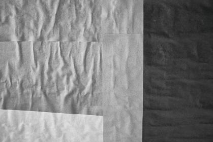 黒灰色のしわくちゃな紙の背景。貼り合わせた四角い紙。古めかしくて怖い汚れたテクスチャ。