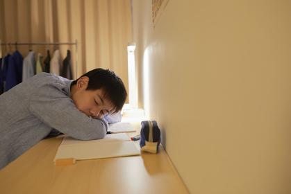 机で居眠りをする男子中学生