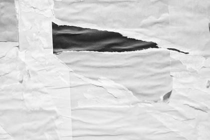 白灰色のしわくちゃな紙の背景。剥がされた紙。古くて汚れた紙のテクスチャ。灰色のテキストスペース。