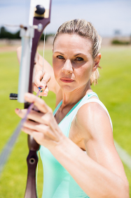 Confident female athlete practicing archery