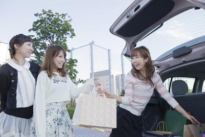 車のトランクから友達にショッピングバッグを渡す笑顔の女性