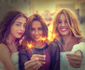 Best friends teen girls with sparklers at sunset in the city filtered image