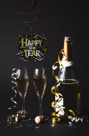 Champagne and Happy New Year sign with black background.