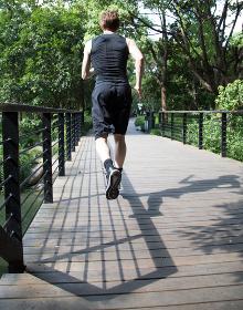 Rear view of man running across bridge