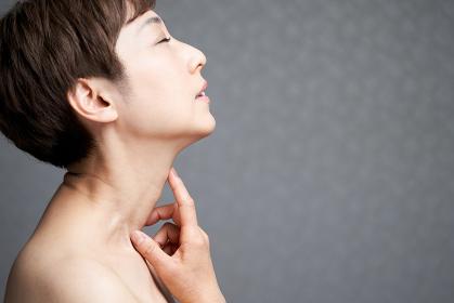 首を押さえる中年の日本人女性