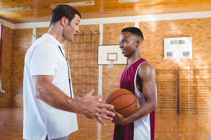 Coach talking with basketball player