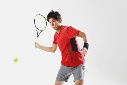 テニスをする若い日本人男性