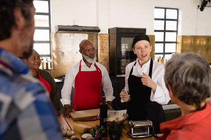 Over the shoulder view of a multi-ethnic group of Senior adults at a cookery class, the diverse adult students listening to instructions from a Caucasian female chef wearing chefs whites and a black hat and apron, standing around a wooden table of ingredients