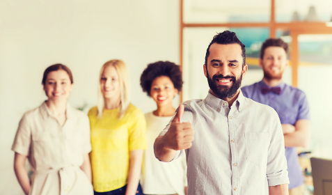 happy man showing thumbs up over team in office