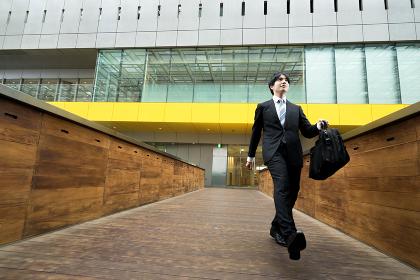 元気に歩くスーツ姿の男性(ビジネスイメージ)