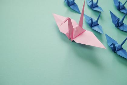 複数の青く小さな折り鶴を率いているピンクの大きな折り鶴。左に青緑のスペースがある。