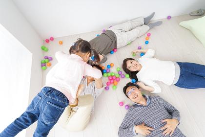 部屋で寝転ぶ三世代の家族