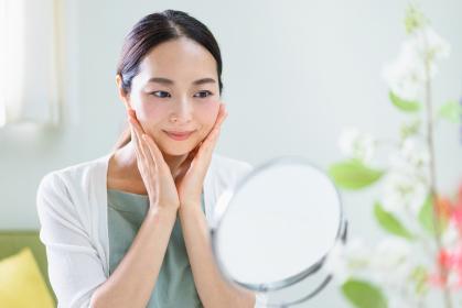 鏡を見てスキンケアをする女性(ビューティーイメージ)