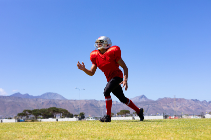 Front view of a mixed race male American football player wearing a team uniform, training at a sports field, looking up and running, preparing to catch a football, with blue sky in the background