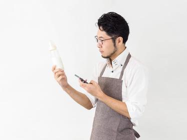 スマホでミルクの作り方を調べる男性のイメージ
