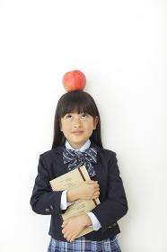 頭にりんごをのせた制服姿の女の子