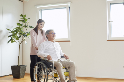 車椅子のシニアの男性を介助する若い女性