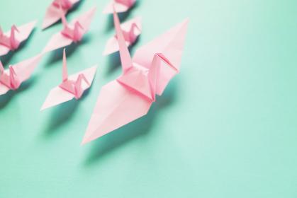 複数のピンクの小さな折り鶴を率いているピンクの大きな折り鶴。右に青緑のスペースがある。