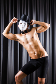 Muscular actor with mask against curtain