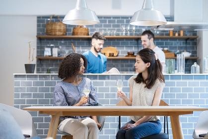 ダイニングテーブルで談笑する女性たちと男性たち