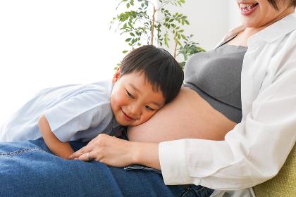 赤ちゃんの鼓動を聞く小さな男の子