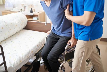 高齢者の介助をする介護士