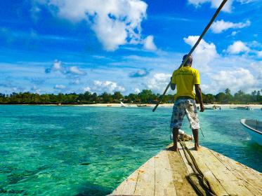 タンザニア・ザンジバル島の海と船を漕ぐアフリカ人