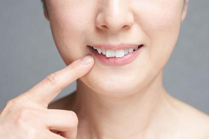 口元を指差す中年の日本人女性