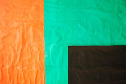 黒、橙色、緑のしわくちゃな紙の背景。貼り合わせた四角い紙。汚れたテクスチャ。